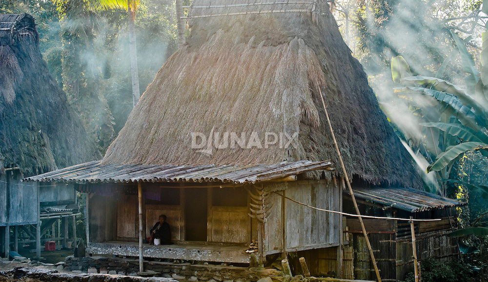 Morning sun filters through smoke around a traditional wooden home with thatched roof, Luba Village, near Bajawa, Flores, Indonesia.