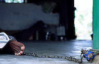 Tamil Nadu, INDIA. March1994..A man has his feet chained to a wall..This is the fate awaiting those, who the locals believe are possessed by evil spirits.
