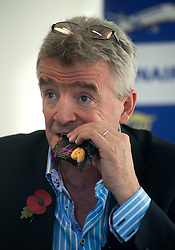 © Licensed to London News Pictures.04/11/2013. London, UK.Michael O'Leary, chief executive officer of Ryanair Holdings Plc opens a pack of biscuits with his  teeth during a media briefing on Ryanair's half year results for the period.Photo credit : Peter Kollanyi/LNP