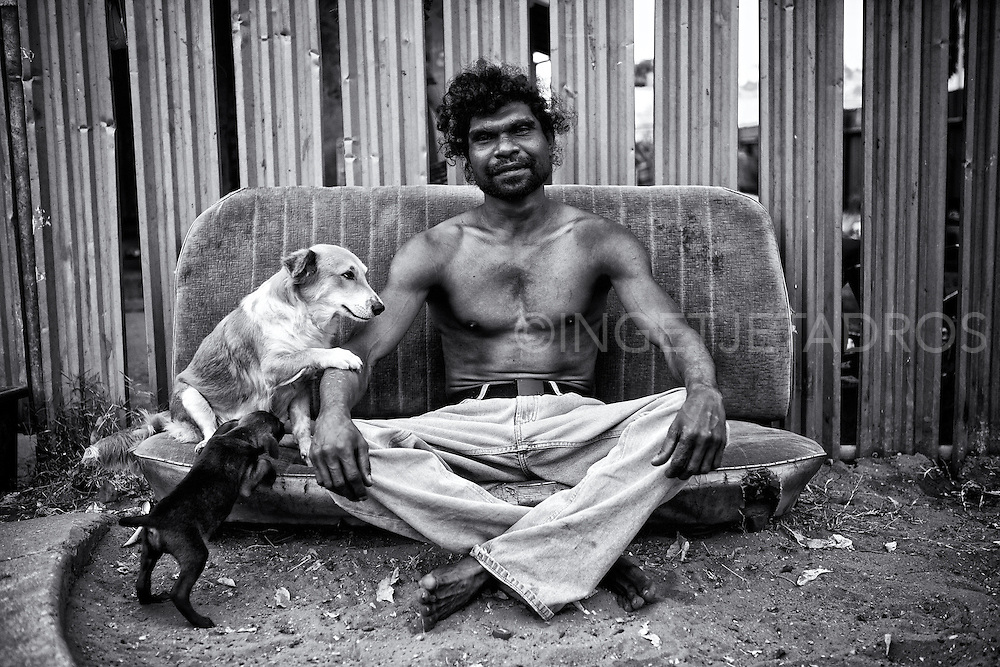 """""""Alcohol can bring you down and kill you, it will....to me I was happy to die, I lost my father he was my hero, I had a bad record , I know now my job is to save my people."""" 'Billy' Stuart Ah Choo sitting outside his home in Kennedy Hill with his beloved dog Dontee and her pup Little Blacky. Broome, Western Australia. ©Ingetje Tadros/Diimex"""