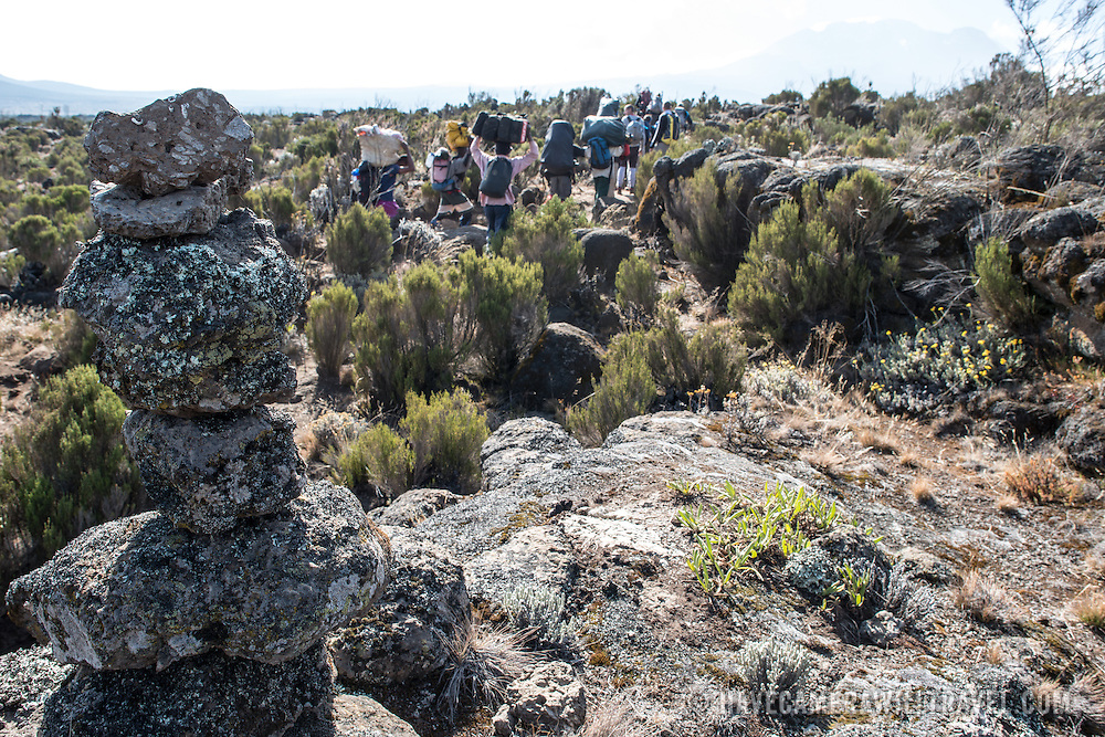 A stone cairn next to the path of the Lemosho Route on Mt Kilimanjaro as a group of porters walk by.