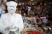 Panjiayuan weekend market. Porcelaine and ceramics. Shop owners having a chat next to a porcelaine bust of Chairman Mao.