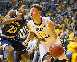Nov 11, 2016; Morgantown, WV, USA; West Virginia Mountaineers guard Chase Harler (14) drives baseline past Mount St. Mary's Mountaineers guard Greg Alexander (23) during the second half at WVU Coliseum. Mandatory Credit: Ben Queen-USA TODAY Sports