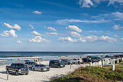 Private vehicles park on the sand along the Flagler Avenue beach in New Smyrna Beach, Florida.