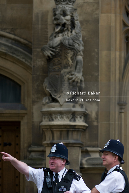 Two Metropolitan police officers talk on duty while guarding Britain's parliament in Westminster, London.