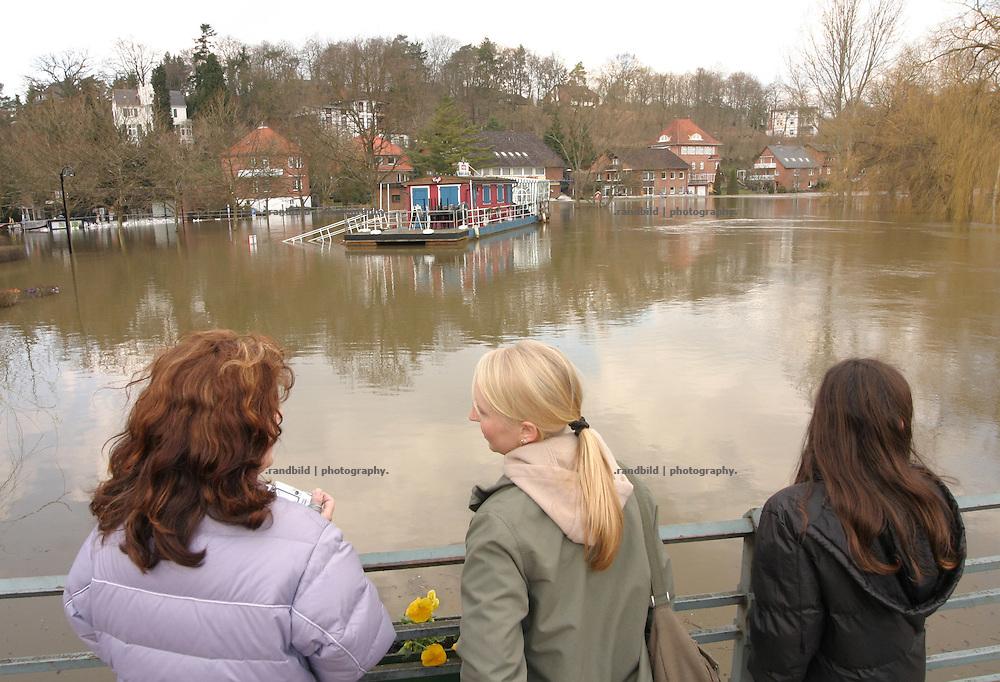 Drei Frauen blicken waehrend des Elbehochwassers von einer Bruecke auf die scheinbar untergegangene Stadt Hitzacker. ..Elbe floods in Hitzacker, Germany.
