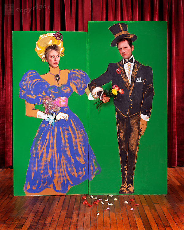 A couple pose with their faces and hands through a nostalgic carnival cut-out painting of a man with tuxedo and top hat and woman with blue dress and hairdo on a stage with red velvet curtain.