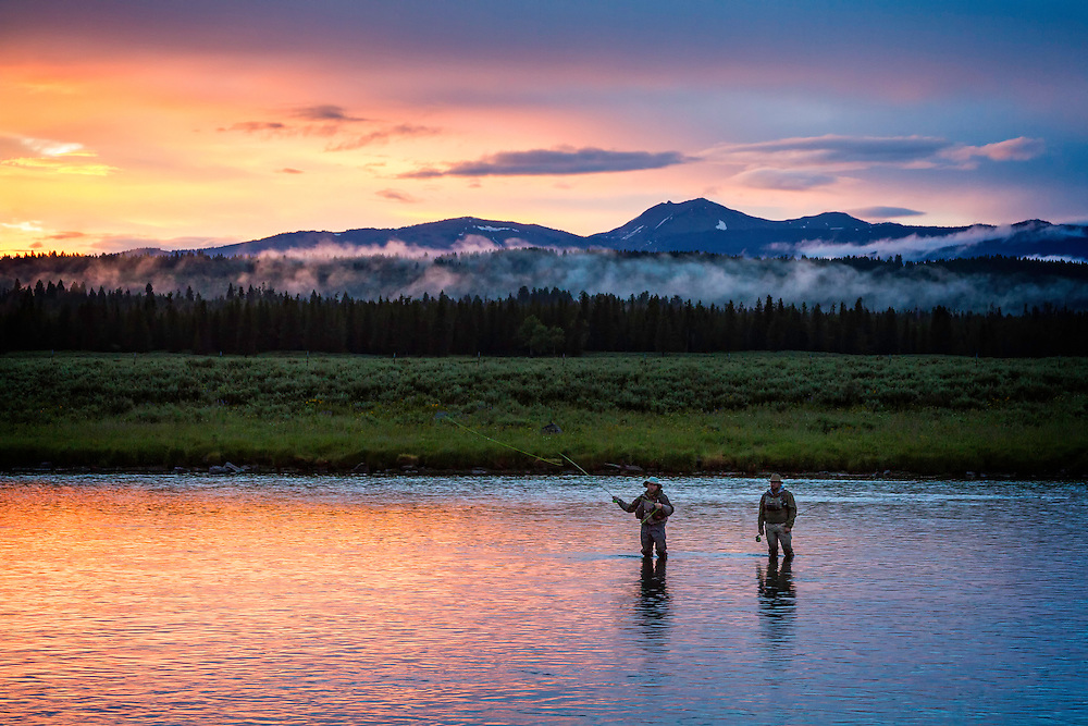 Two fly fisherman fishing the Henry's Fork River near Last Chance, ID as the sunset colors illuminate the water and surrounding hills.