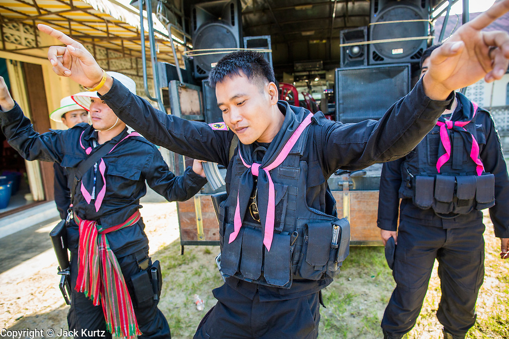 31 OCTOBER 2012 - YARANG, PATTANI, THAILAND: Thai soldiers dance and relax before in the temple before escorting villagers from Wat Kohwai on a procession to Yala for Ok Phansa. Ok Phansa marks the end of the Buddhist 'Lent' and falls on the full moon of the eleventh lunar month (October). It's a day of joyful celebration and merit-making. For the members of Wat Kohwai, in Yarang District of Pattani, it was a even more special because it was the first time in eight years they've been able to celebrate Ok Phansa. The Buddhist community is surrounded by Muslim villages and it's been too dangerous to hold the boisterous celebration because of the Muslim insurgency that is very active in this area. This the year the Thai army sent a special group of soldiers to secure the village and accompany the villagers on their procession to Yala, a city  about 20 miles away.   PHOTO BY JACK KURTZ