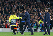 Pitch invader is escorted away by a steward and security with Tottenham Hotspur Manager Mauricio Pochettino looking on during the Champions League Quarter-Final 1st leg between Tottenham Hotspur and Manchester City at Tottenham Hotspur Stadium, London, United Kingdom on 9 April 2019.