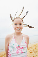 Pre-teen girl standing on beach with feathers in hair portrait