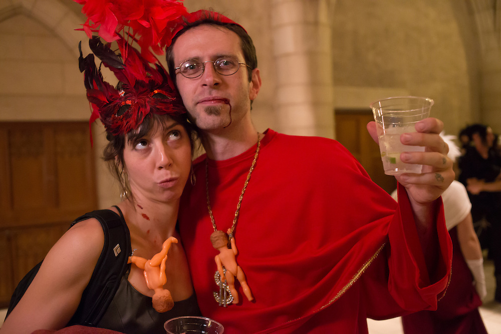 A man dressed as a cardinal, with blood dripping from a corner of his mouth, and a woman with a mask.