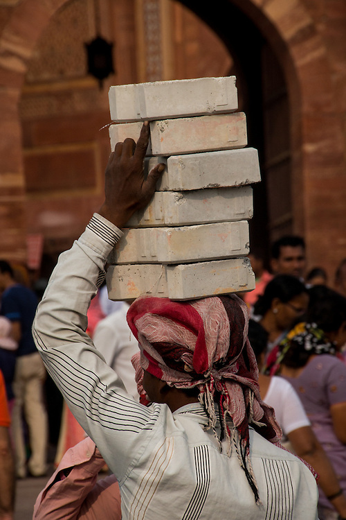 People of India use their heads to carry objects from place to place.  In this photo a man is using his head to move bricks to a construction site.