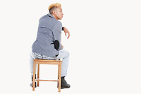 Back view of teenage boy sitting on chair as he looks away over gray background
