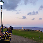 SAN JUAN, PUERTO RICO -- JANUARY 1, 2019: <br /> Samuel Garcia, 57, a professional musician plays his tenor saxophone along to music playing from his car as the  sun goes down in Castillo San Felipe del Morro also known as Fuerte San Felipe del Morro or Castillo del Morro in Historic Old San Juan.<br /> (Photo by Angel Valentin)