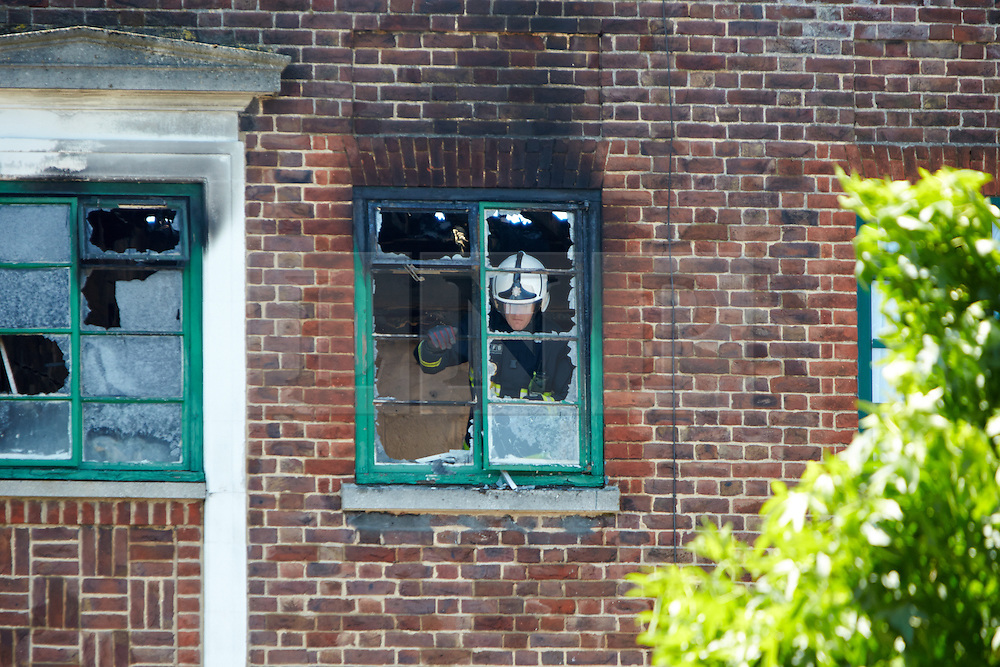© Licensed to London News Pictures.  10/07/2013. LONDON, UK. Fire crews at the scene of a fatal house fire in a flat above a shop on New Heston Road (Church Road), Hounslow. Two men and a woman jumped from the building before fire crews arrived. The woman, thought to be 30 years old, died at the scene and another body was discovered inside. Photo credit: Cliff Hide/LNP
