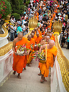 "22 JULY 2013 - PHRA PHUTTHABAT, THAILAND: Buddhist monks climb the stairway to the Mondop (chapel that houses the footprint) before the Tak Bat Dok Mai at Wat Phra Phutthabat in Saraburi province of Thailand, Monday, July 22. Wat Phra Phutthabat is famous for the way it marks the beginning of Vassa, the three-month annual retreat observed by Theravada monks and nuns. The temple is highly revered in Thailand because it houses a footstep of the Buddha. On the first day of Vassa (or Buddhist Lent) people come to the temple to ""make merit"" and present the monks there with dancing lady ginger flowers, which only bloom in the weeks leading up Vassa. They also present monks with candles and wash their feet. During Vassa, monks and nuns remain inside monasteries and temple grounds, devoting their time to intensive meditation and study. Laypeople support the monastic sangha by bringing food, candles and other offerings to temples. Laypeople also often observe Vassa by giving up something, such as smoking or eating meat. For this reason, westerners sometimes call Vassa the ""Buddhist Lent.""       PHOTO BY JACK KURTZ"