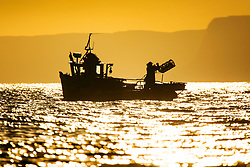 © Licensed to London News Pictures. 12/11/2018. Scarborough UK. A fisherman throws a lobster pot from his boat at sunrise this morning in Scarborough on the Yorkshire coast. Photo credit: Andrew McCaren/LNP
