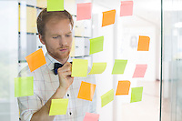 Creative businessman writing on sticky paper at office