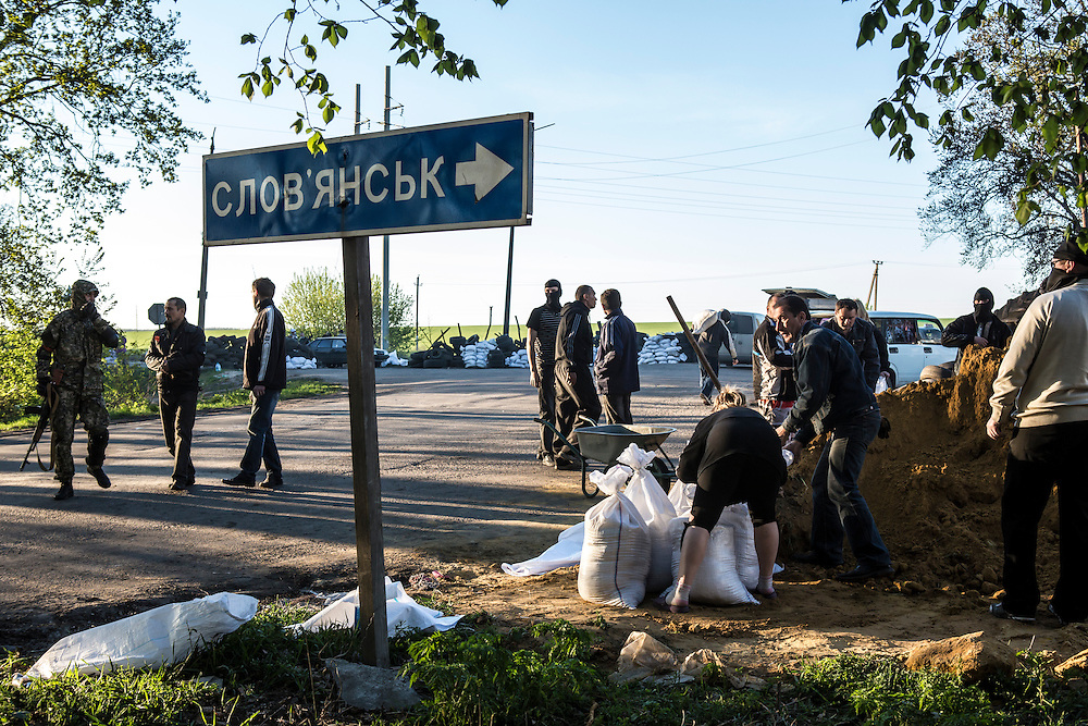 SLOVYANSK, UKRAINE - APRIL 24:  Pro-Russian separatist militants fill sand bags to reinforce a checkpoint on April 24, 2014 in Slovyansk, Ukraine. Pro-Russian activists have been occupying government buildings and demanding greater autonomy in many Eastern Ukrainian cities in recent weeks, prompting the government in Kiev to threaten military action to retake control of the cities. (Photo by Brendan Hoffman/Getty Images) *** Local Caption ***