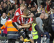 Brentford players celebrate with Brentford's Stuart Dallas after scoring the winner 2-1 during the Sky Bet Championship match between Brentford and Derby County at Griffin Park, London, England on 1 November 2014.