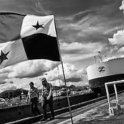 """MIRAFLORES LOCKS - PANAMA CANAL<br /> Photography by Aaron Sosa<br /> Panama City, Panama 2012<br /> (Copyright © Aaron Sosa)<br /> <br /> """"Canaleros"""" walk to your workplace. In the background can be seen one of the big boats that cross the Panama Canal.<br /> <br /> The Panama Canal is an 77.1-kilometre (48 mi) ship canal in Panama that connects the Atlantic Ocean (via the Caribbean Sea) to the Pacific Ocean. The canal cuts across the Isthmus of Panama and is a key conduit for international maritime trade. There are locks at each end to lift ships up to Lake Gatun (26m (85ft) above sea-level) which was used to reduce the amount of work required for a sea-level connection. The current locks are 33.5m (110ft) wide although new larger ones are proposed.<br /> <br /> Work on the canal, which began in 1881, was completed in 1914, making it no longer necessary for ships to sail the lengthy Cape Horn route around the southernmost tip of South America (via the Drake Passage) or to navigate the dangerous waters of the Strait of Magellan. One of the largest and most difficult engineering projects ever undertaken, the Panama Canal shortcut made it possible for ships to travel between the Atlantic and Pacific Oceans in half the time previously required. The shorter, faster, safer route to the U.S. West Coast and to nations in and along the Pacific Ocean allowed those places to become more integrated with the world economy."""