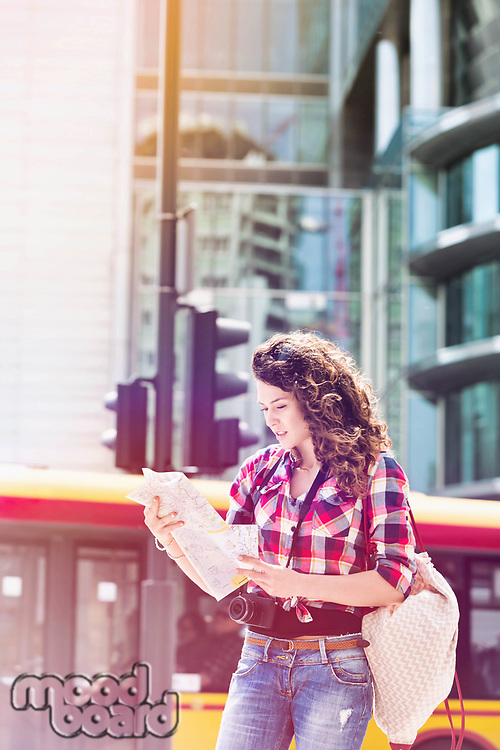 Portrait of young attractive woman looking on the map in the city with lens flare in background