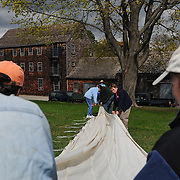 Rolling up the sail to carry it onto the Gundalow