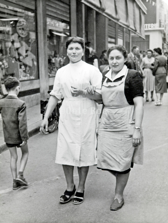 two female shop workers strolling in a shopping street France 1950s