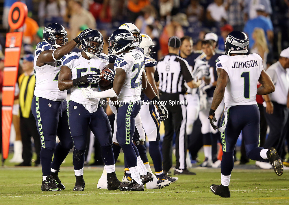 Seattle Seahawks rookie linebacker Tyrell Adams (53) gets a pat on the helmet from a teammate and congratulations from Seattle Seahawks rookie cornerback Tye Smith (22) after Adams intercepts a pass on the final play of the game during the 2015 NFL preseason football game against the San Diego Chargers on Saturday, Aug. 29, 2015 in San Diego. The Seahawks won the game 16-15. (©Paul Anthony Spinelli)