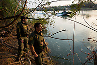 Border patrol agents look across the Rio Grande river as a border patrol boat goes by, in Roma, TX, on the U.S.-Mexico border, on February 2, 2017 (Photo/Scott Dalton)