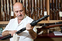 Mature gun shop merchant looking at rifle in store