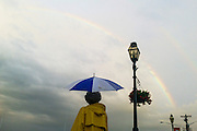 """Annapolis, Maryland - June 05, 2016: Cynthia Chess, from Annapolis checks out a rainbow during a light shower in the Dock Street area of Historic Annapolis, Md., Sunday June 5th, 2016. Annapolis is one of the most prone cities in the U.S. to nuisance flooding. <br /> <br /> <br /> A perigean spring tide brings nuisance flooding to Annapolis, Md. These phenomena -- colloquially know as a """"King Tides"""" -- happen three to four times a year and create the highest tides for coastal areas, except when storms aren't a factor. Annapolis is extremely susceptible to nuisance flooding anyway, but the amount of nuisance flooding has skyrocketed in the last ten years. Scientists point to climate change for this uptick. <br /> <br /> <br /> CREDIT: Matt Roth for The New York Times<br /> Assignment ID: 30191272A"""