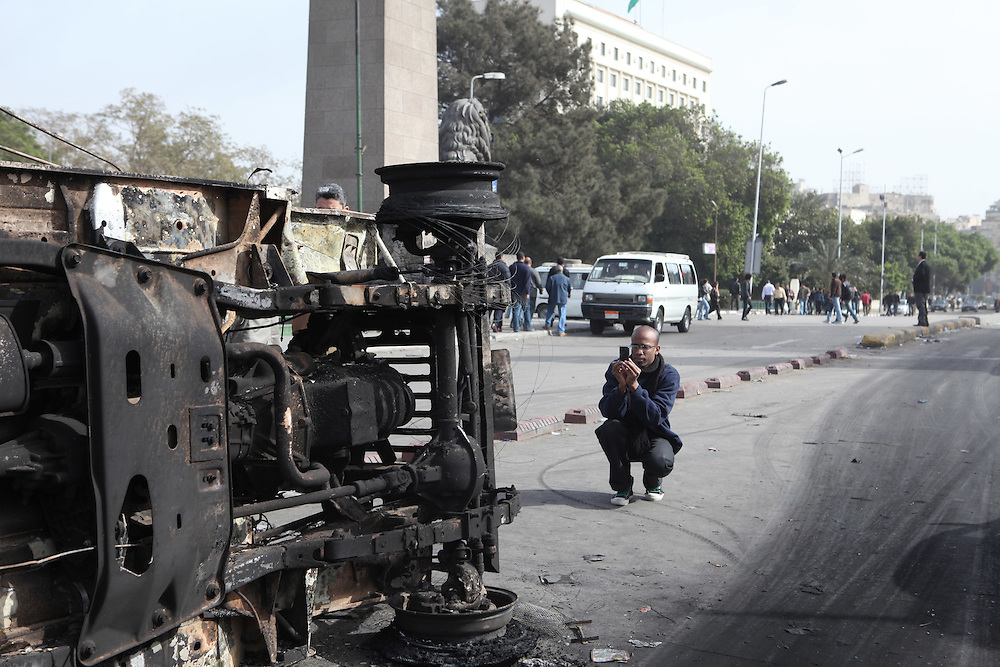 A man takes a picture of an army jeep a day after it was destroyed by protesters.