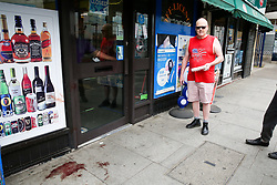 © Licensed to London News Pictures. 25/04/2019. London, UK. A man views the blood stains outside Hill's New Point newsagent on Leytonstone High Road, Waltham Forest in East London. Two men were stabbed multiple times at a bus stop next to Hill's New Point newsagent close to Leytonstone High Road overground station just before 8pm on Wednesday 24 April 2019. A man in his 20s remains in a hospital in a critical condition. Photo credit: Dinendra Haria/LNP