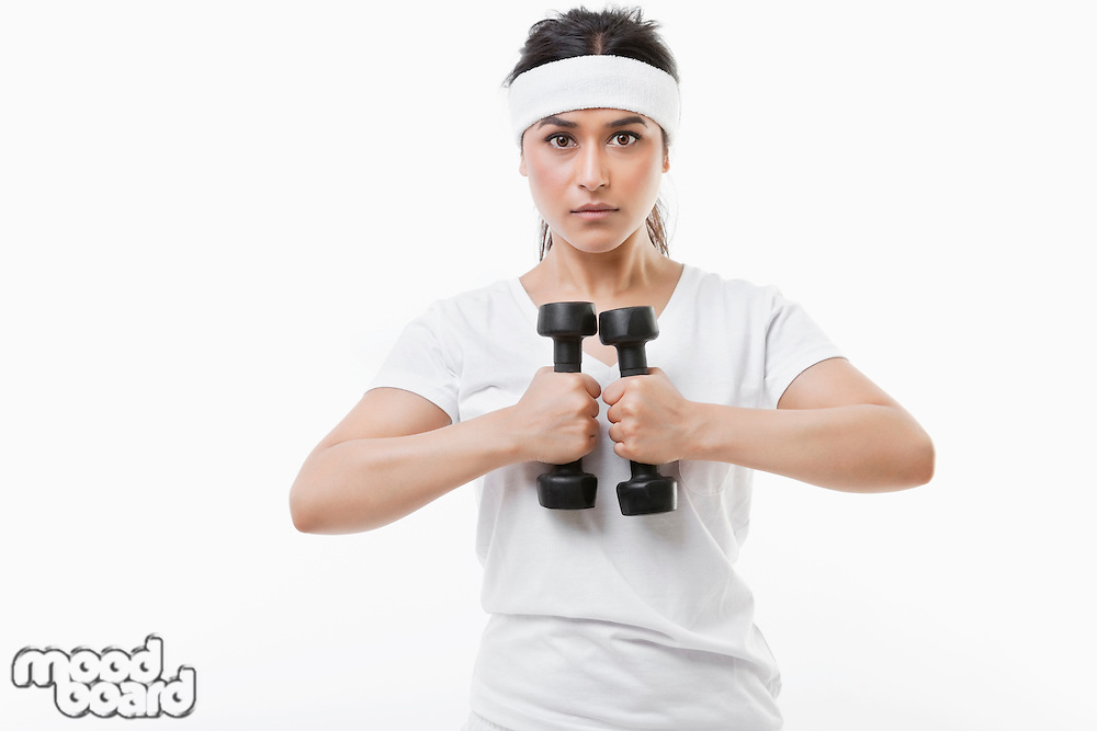 Portrait of young Asian sportswoman raising dumbbell over white background