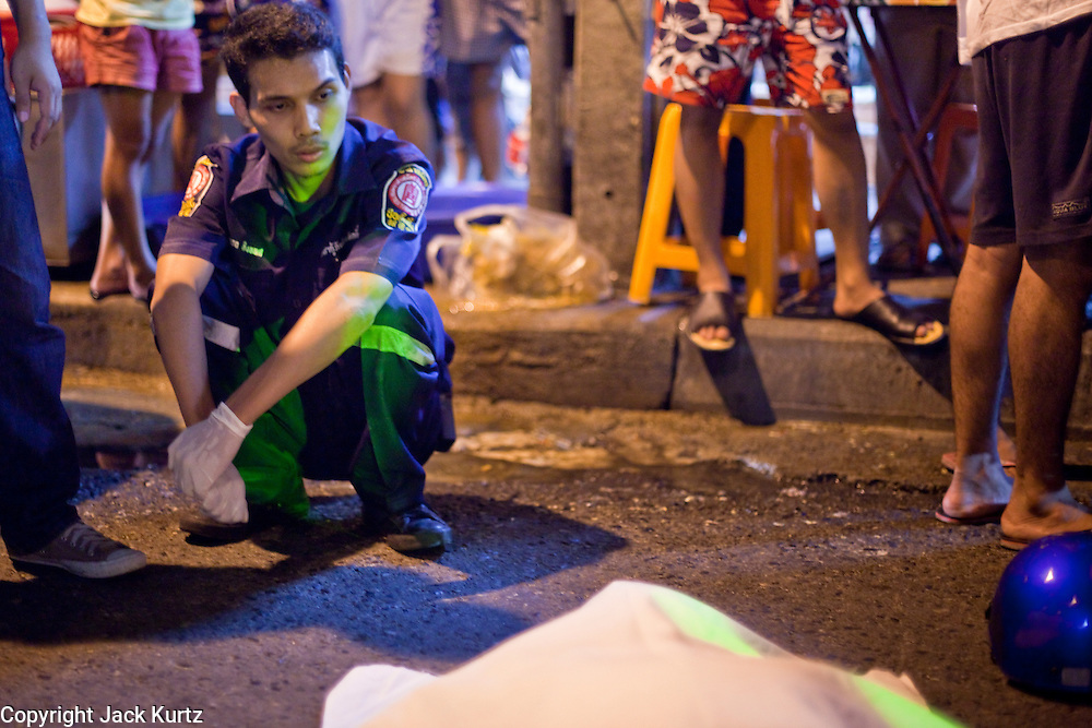 """Oct. 2, 2009 -- BANGKOK, THAILAND:  A volunteer from the Poh Teck Tung Foundation sits on the side of a Bangkok street after trying in vain to save a man's life after a motorcycle accident. The 1,000 plus volunteers of the Poh Teck Tung Foundation are really Bangkok's first responders. Famous because they pick up the dead bodies after murders, traffic accidents, suicides and other unplanned, often violent deaths, they really do much more. Their medics respond to medical emergencies, from minor bumps and scrapes to major trauma. Their technicians respond to building collapses and traffic accidents with heavy equipment and the """"Jaws of Life"""" and their divers respond to accidents in the rivers and khlongs of Bangkok. The organization was founded by Chinese immigrants in Bangkok in 1909. Their efforts include a hospital, college tuition for the poor and tsunami relief.    Photo by Jack Kurtz / ZUMA Press"""