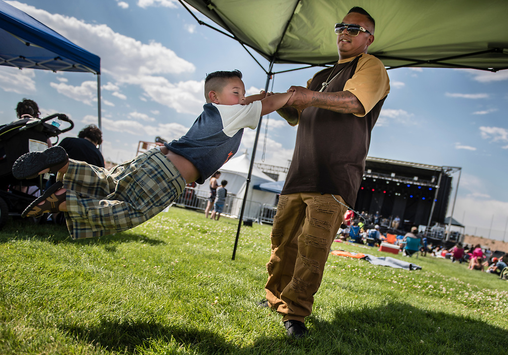 rer070417l/metro/July 04, 2017/Albuquerque Journal<br /> Greg Gallegos(Cq) swings his son Jayden Gallegos(cq),3,  at Balloon Fiesta Park Tuesday afternoon. They were there to witness perhaps the best firework display in the state st to go off at a little past 9pm. <br /> Albuquerque, New Mexico Roberto E. Rosales/Albuquerque Journal