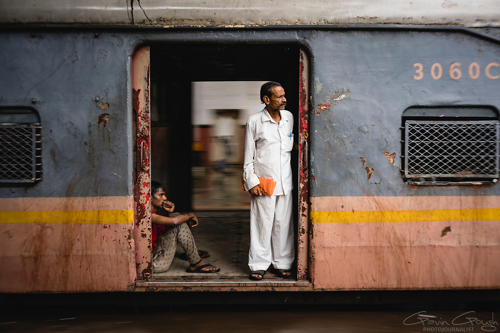 Two men look out of an open train doorway as their train departs Mumbai's Chhatrapati Shivaji Terminus station.