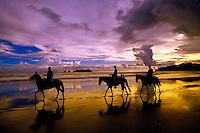 Horseback riding on Playa Espadilla Norte (beach) with the sun setting in the distance, Manuel Antonio, Costa Rica