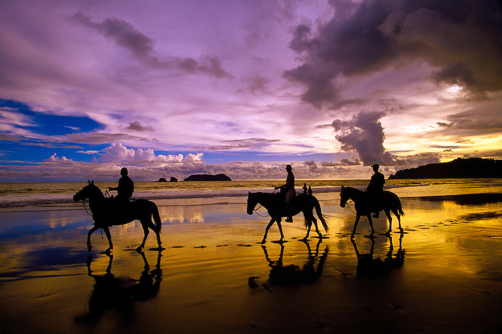 Horseback riding on Playa Espadilla Norte (beach) with the sun setting in the distance, Manuel Antonio, Costa Rica