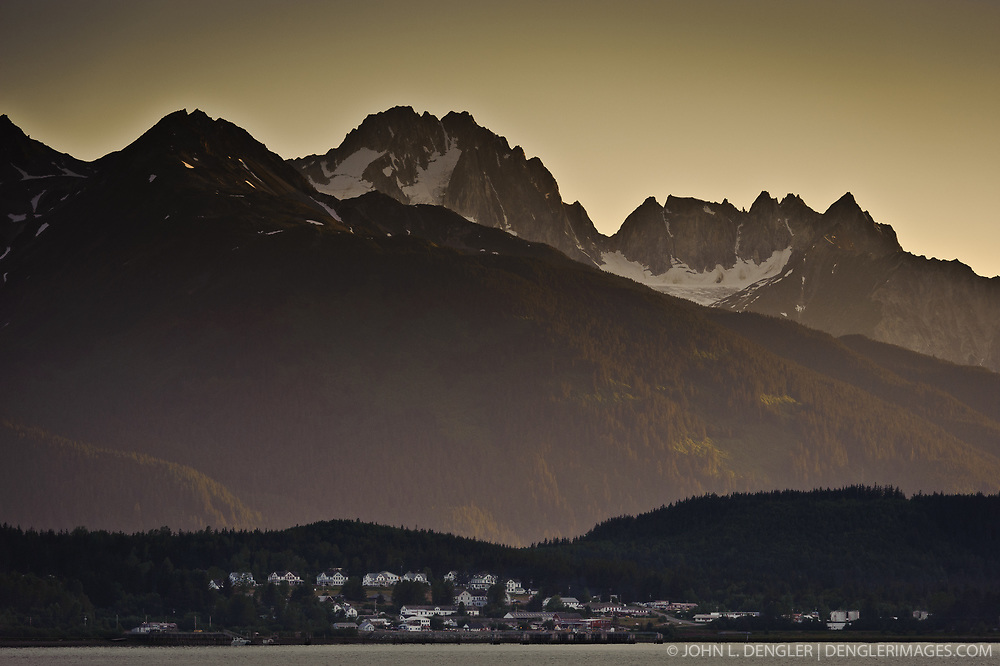The historic buildings of the former U.S. Army facility, Fort William H. Seward in Haines, Alaska are dwarfed by Mount Emmerich and other peaks of the Takhinsha Mountains as the setting sun lights up the Chilkat River valley. Haines is a cruise ship destination on the Lynn Canal in southeast Alaska. Cruise ships dock at the pictured Port Chilkoot dock near downtown Haines.