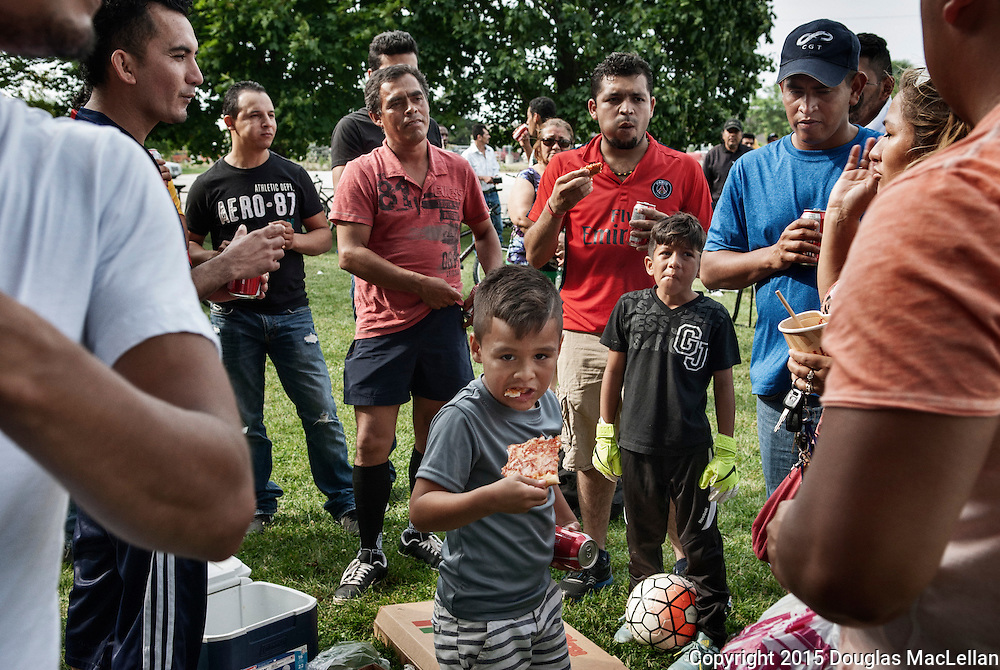 A boy eats pizza along with others after a quarter final soccer game in a field near the Leamington fairgrounds. The league, operated by Leamington greenhouse and farm owners, features mostly migrant workers.