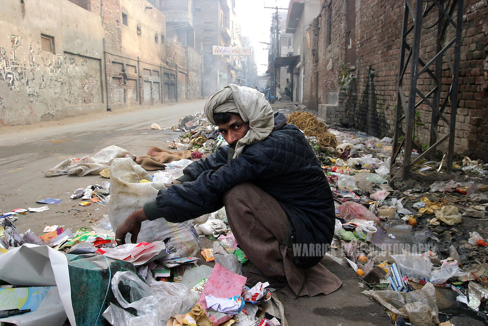 A heroin addict searches through garbage for something of value to sell in order to buy heroin. Heroin is cheap and readily available in Pakistan due to it's proximity to Afghanistan which supplies almost 90% of heroin to Europe, December 11, 2004, Lahore, Pakistan. Almost 20% of heroin produced in Afghanistan is trafficked through Pakistan according to the UN Office on Drugs and Crime (UNODC). With the fall of the Taliban, opium cultivation has risen dramatically in spite of Afghan and coalition forces attempts to stem production. Pakistan has between 3.5-4 million heroin users, one of the highest numbers of heroin users in the world, next to Iran. (Photo by Warrick Page)