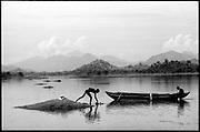 Sri Lanka.<br /> Two men and a boat at Giritale irrigation tank.<br /> Copyright: Dominic Sansoni