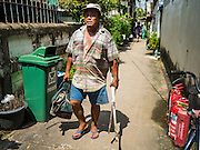 16 OCTOBER 2015 - BANGKOK, THAILAND: A man walks out of the Wat Kalayanamit neighborhood. Fifty-four homes around Wat Kalayanamit, a historic Buddhist temple on the Chao Phraya River in the Thonburi section of Bangkok, are being razed and the residents evicted to make way for new development at the temple. The abbot of the temple said he was evicting the residents, who have lived on the temple grounds for generations, because their homes are unsafe and because he wants to improve the temple grounds. The evictions are a part of a Bangkok trend, especially along the Chao Phraya River and BTS light rail lines. Low income people are being evicted from their long time homes to make way for urban renewal.    PHOTO BY JACK KURTZ