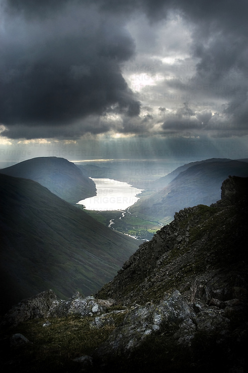 Sun breaking through clouds over a mountainous landscape with lakes
