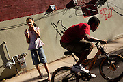 BETHLEHEM, PA – JUNE 2, 2011: Julio Gonzalez, age 15, and Leo Herrandes, age 13, play on their bikes at the junction of Mechanic and State Street in Bethlehem, Pennsylvania, while Annelisses Tejada, age 10, and Jaedyn Lawon, age 6, looks after Annelisses' chihuaha, Buster.<br /> <br /> As the population of second and third generation Hispanics increases dramatically in the United States, a new boldness can be sensed among Latinos in America, stretching far beyond the southern border states. Demographers in Pennsylvania say the towns of Bethlehem, Allentown and Reading are set to become majority-minority cities, where Hispanics comprise a bigger portion of the population than whites. As this minority population increases dramatically in the region, Latinos are inching closer to their own realization of the American Dream, while gradually shifting the physical and cultural landscapes of their communities.