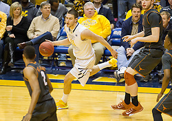 West Virginia Mountaineers guard Nathan Adrian (11) dribbles the ball around a defender against the Texas Longhorns during the second half at the WVU Coliseum.