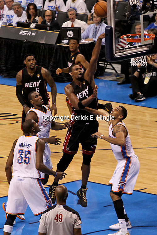 Jun 14, 2012; Oklahoma City, OK, USA;  Miami Heat power forward Chris Bosh (1) shoots over Oklahoma City Thunder power forward Serge Ibaka (9), small forward Kevin Durant (35) and shooting guard Thabo Sefolosha (2)during the second quarter of game two in the 2012 NBA Finals at Chesapeake Energy Arena. Mandatory Credit: Derick E. Hingle-US PRESSWIRE